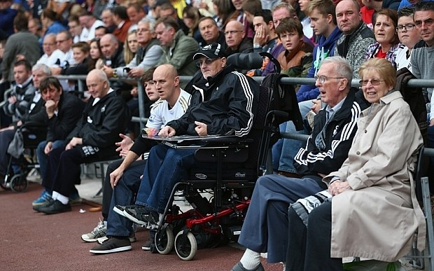 Football fans at match including a fan who is also a wheelchair user.
