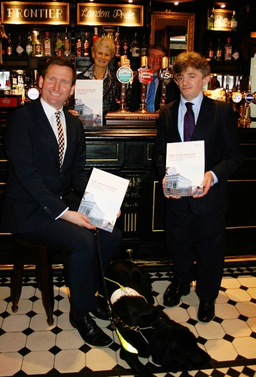 Lord (Chris) Holmes, Lord Shinkwin holding accessible guide to pubs and starting in front of bar in a pub. Guide dog Lottie on floor.