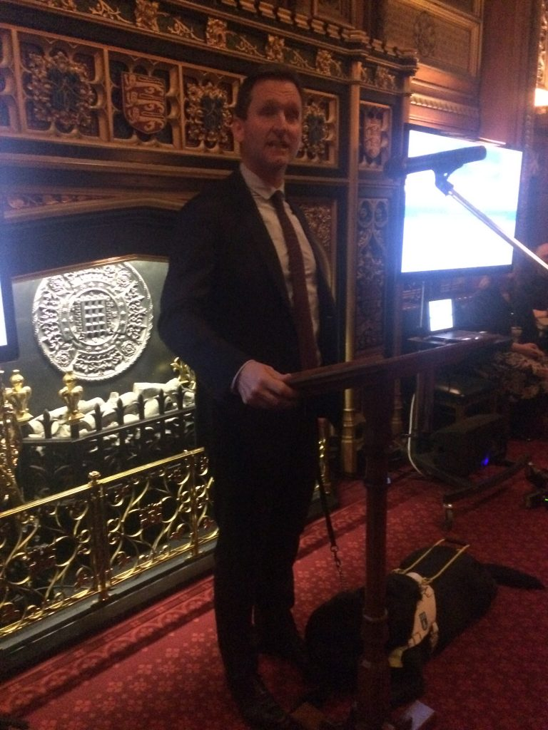 Chris in front of ornate fireplace with microphone and lectern.