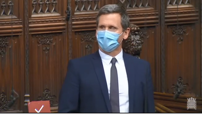 Chris in the House of Lords Chamber, standing to speak in Financial Services Bill debate. Wearing a covid facemask.