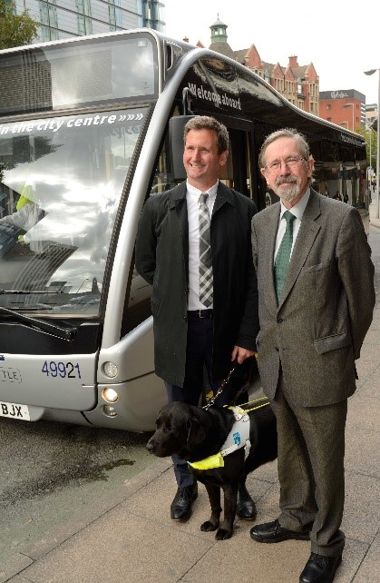 Chris, guide dog Lottie and representative from Manchester Metroshuffle Bus Service standing in front of a bus in Manchester