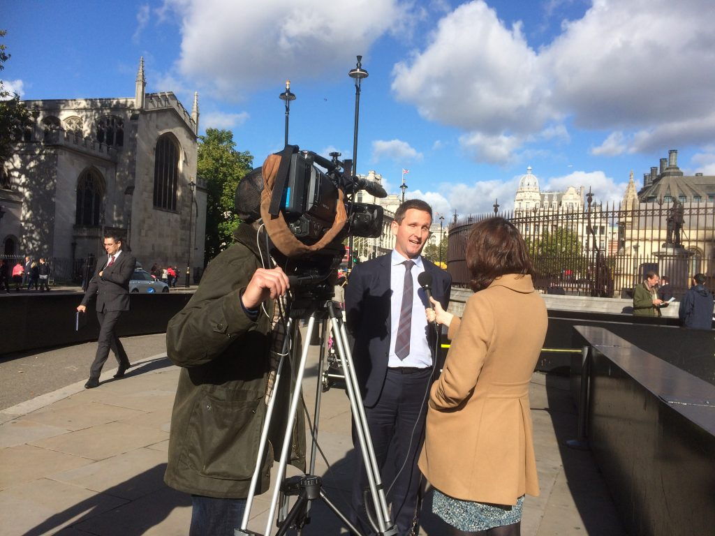 Chris speaking to a BBC journalist about accessible stadia. Cameraman filming. Standing on pavement outside the Palace of Westminster